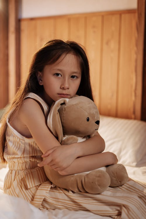 Young Girl Sitting on Bed Hugging Teddy Bear