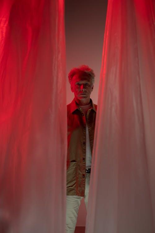 Elderly Man Standing behind Red Curtain