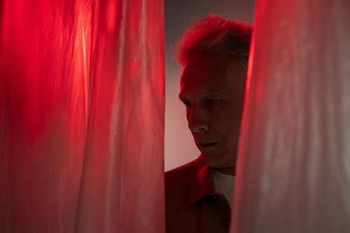 Elderly Man Looking Right behind Red Curtain