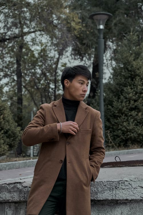 Young Man in Autumn Coat Leaning against Wall