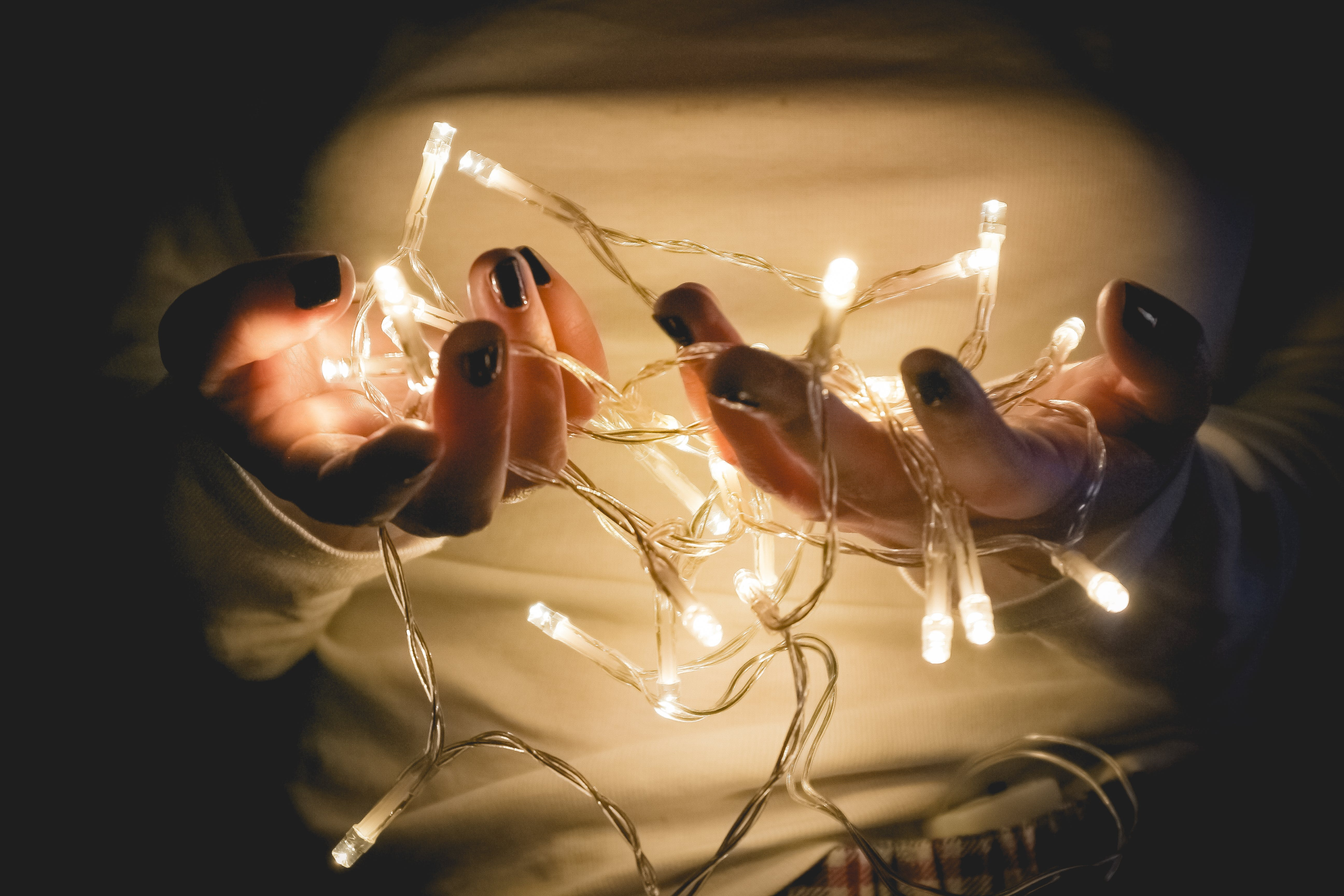 Closeup Photo of Person Wearing White Long-sleeved Shirt Holding Turned on String Lights