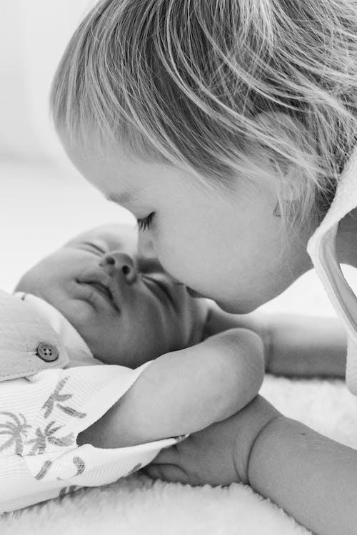 Premature Child Kissing a New Born
