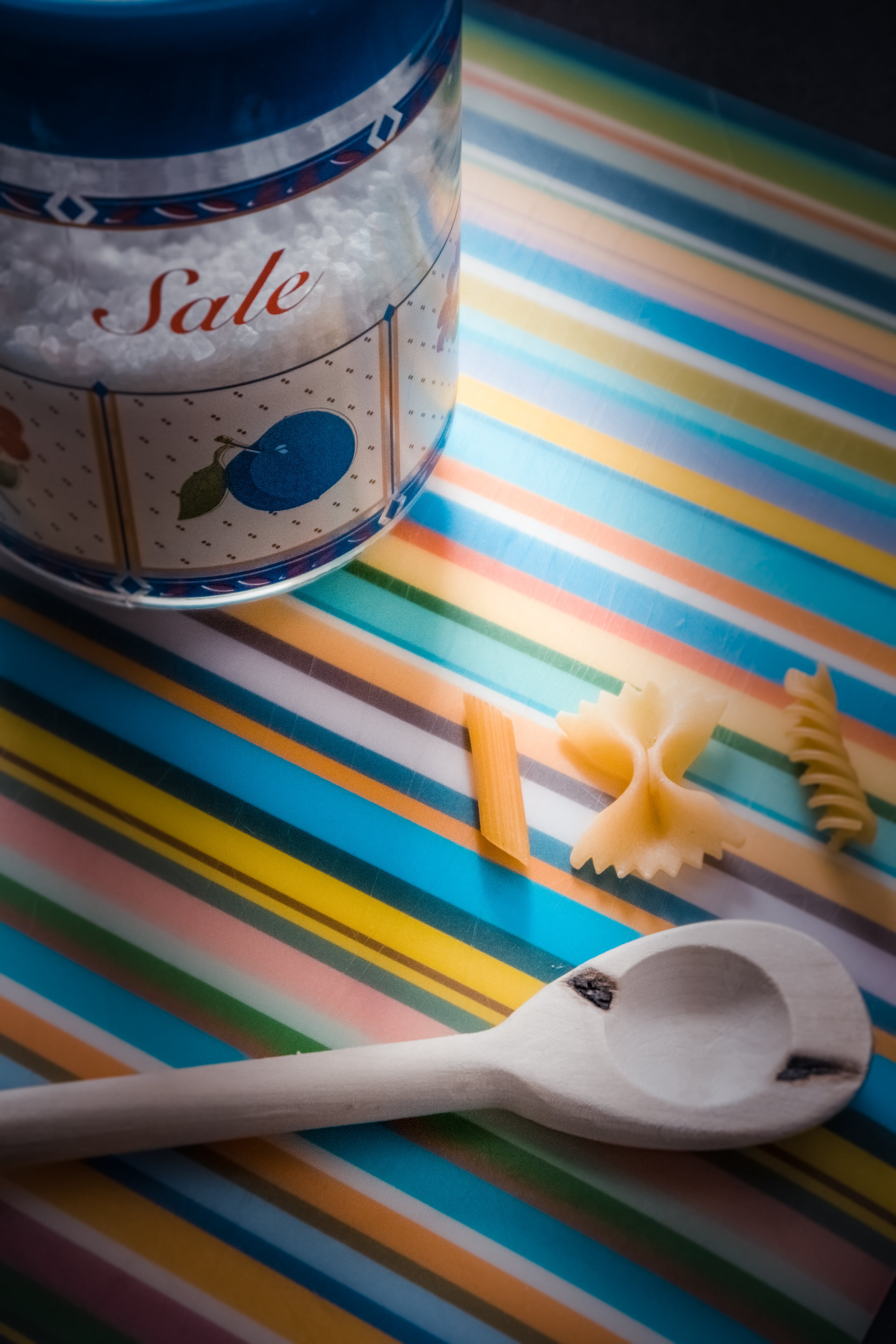 White Wooden Serving Spoon on Multicolored Textile