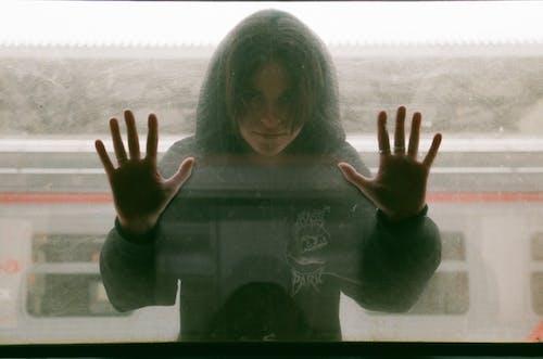 Teenage Girl in Black Hooded Blouse Looking Through Train Window
