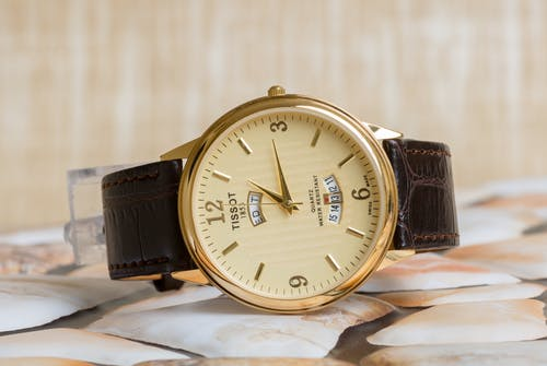 An Analog Gold Watch with Leather Strap
