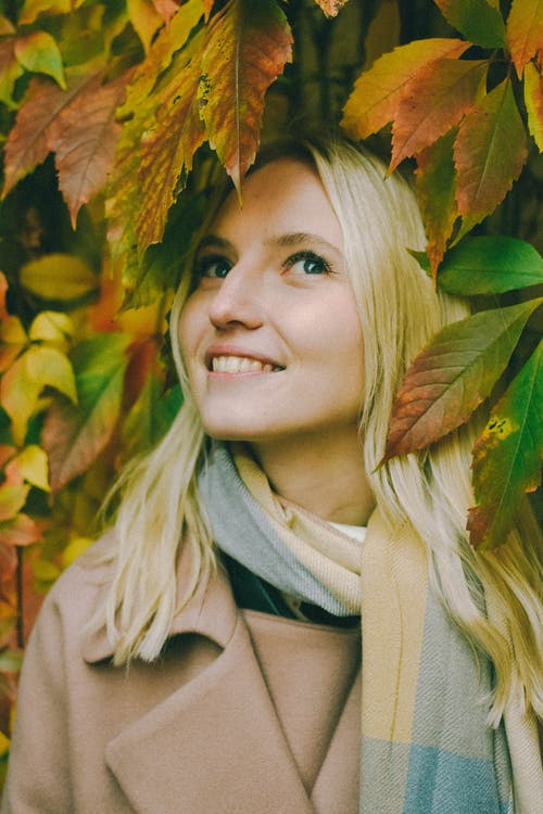 A Female Smiling and Looking Up Between Autumn Leaves