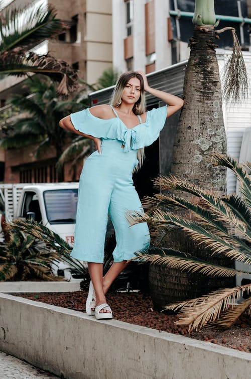 Blond Woman in Turquoise Jumpsuit Leaning Against Big Tree in Street and Posing