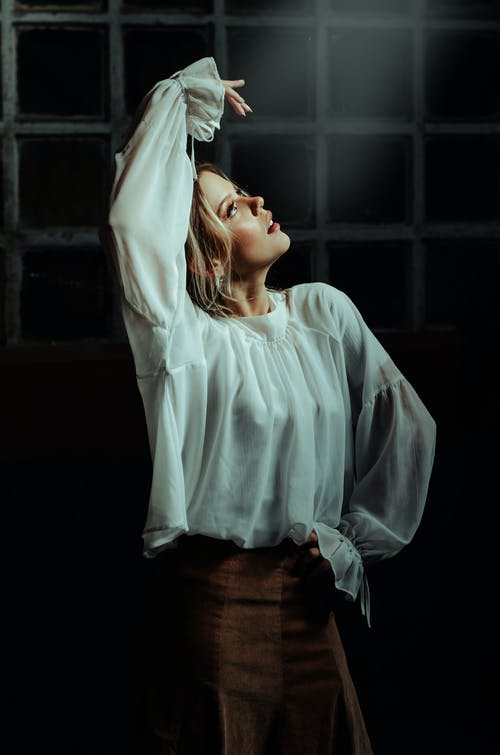 Blond Woman Standing in Ballet Pose with Arm Raised