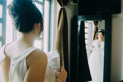 Woman in White Sleeveless Dress Holding White Textile