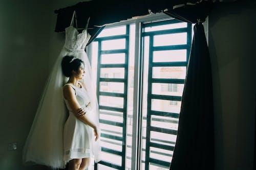 Woman in White Sleeveless Dress Standing Beside Glass Window
