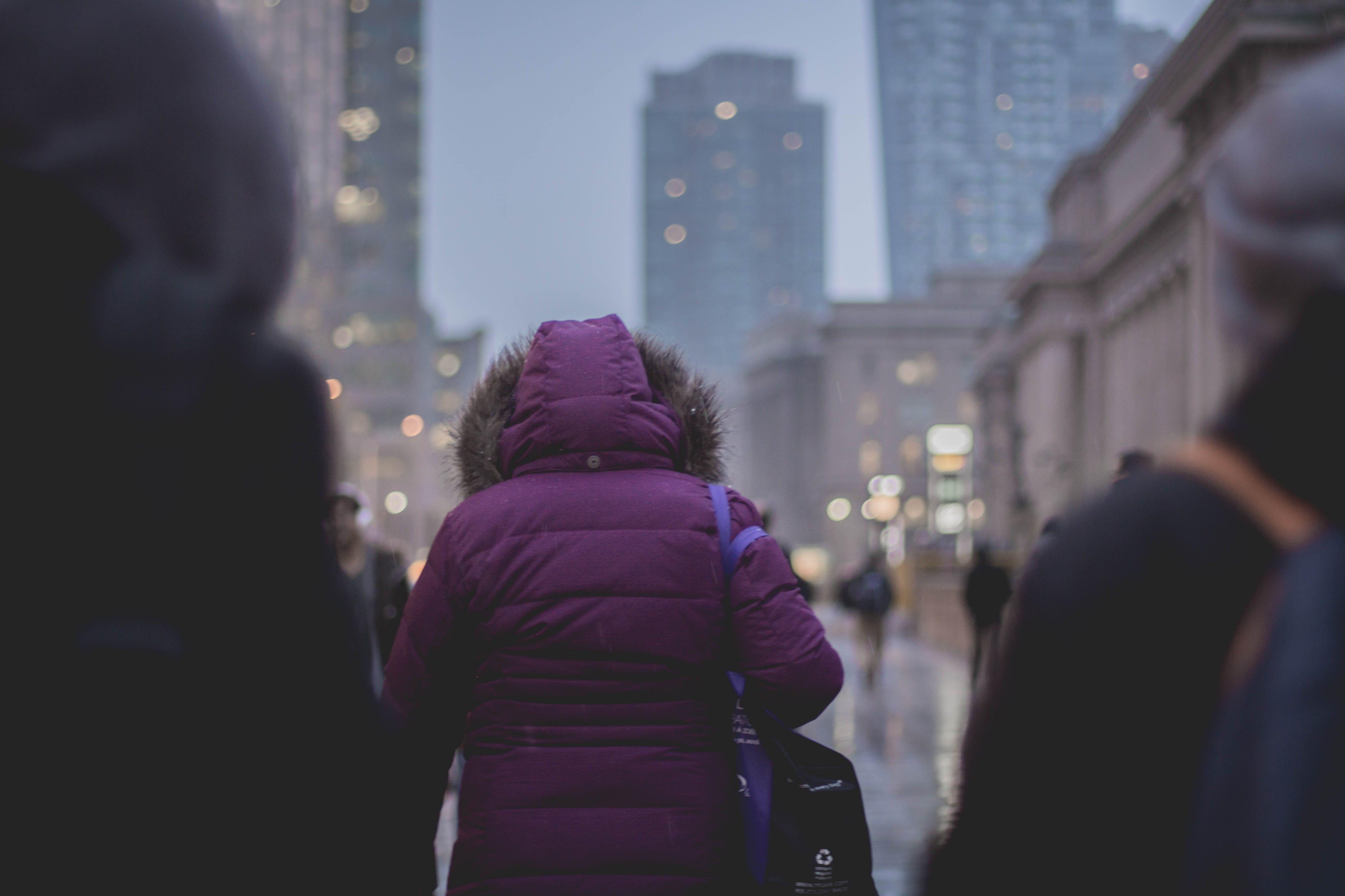 Selective Focus Photograph of Person Wearing Purple Hoodie Jacket Walking on Street