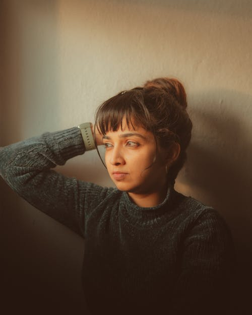 Woman Looking Away and Holding her Head