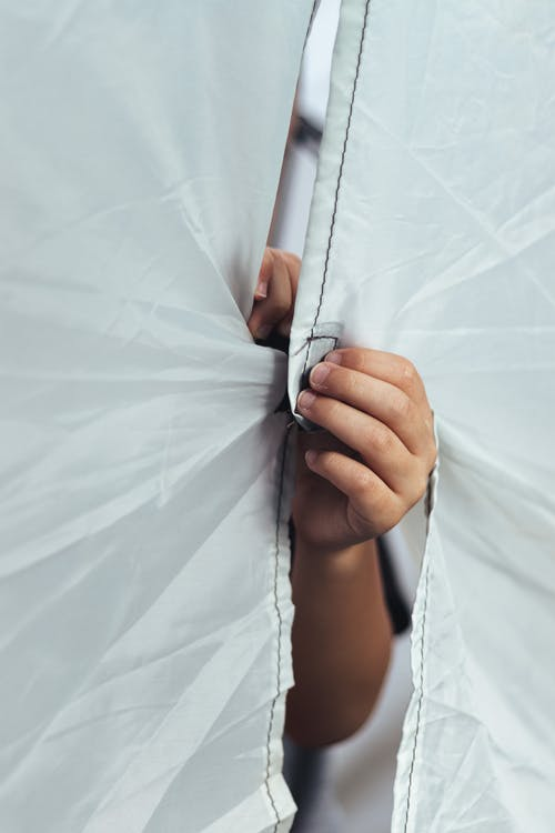 Two Hands Fastening Edges of White Textile with Velcro