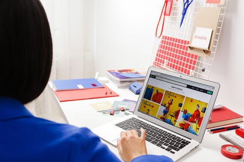 Rear View of Woman in Blue Jacket Working on Laptop