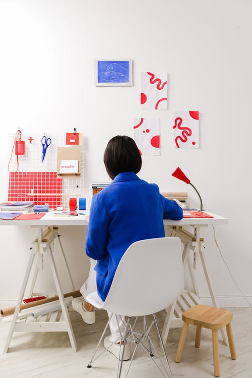 Rear View of Sitting Woman in Work Space