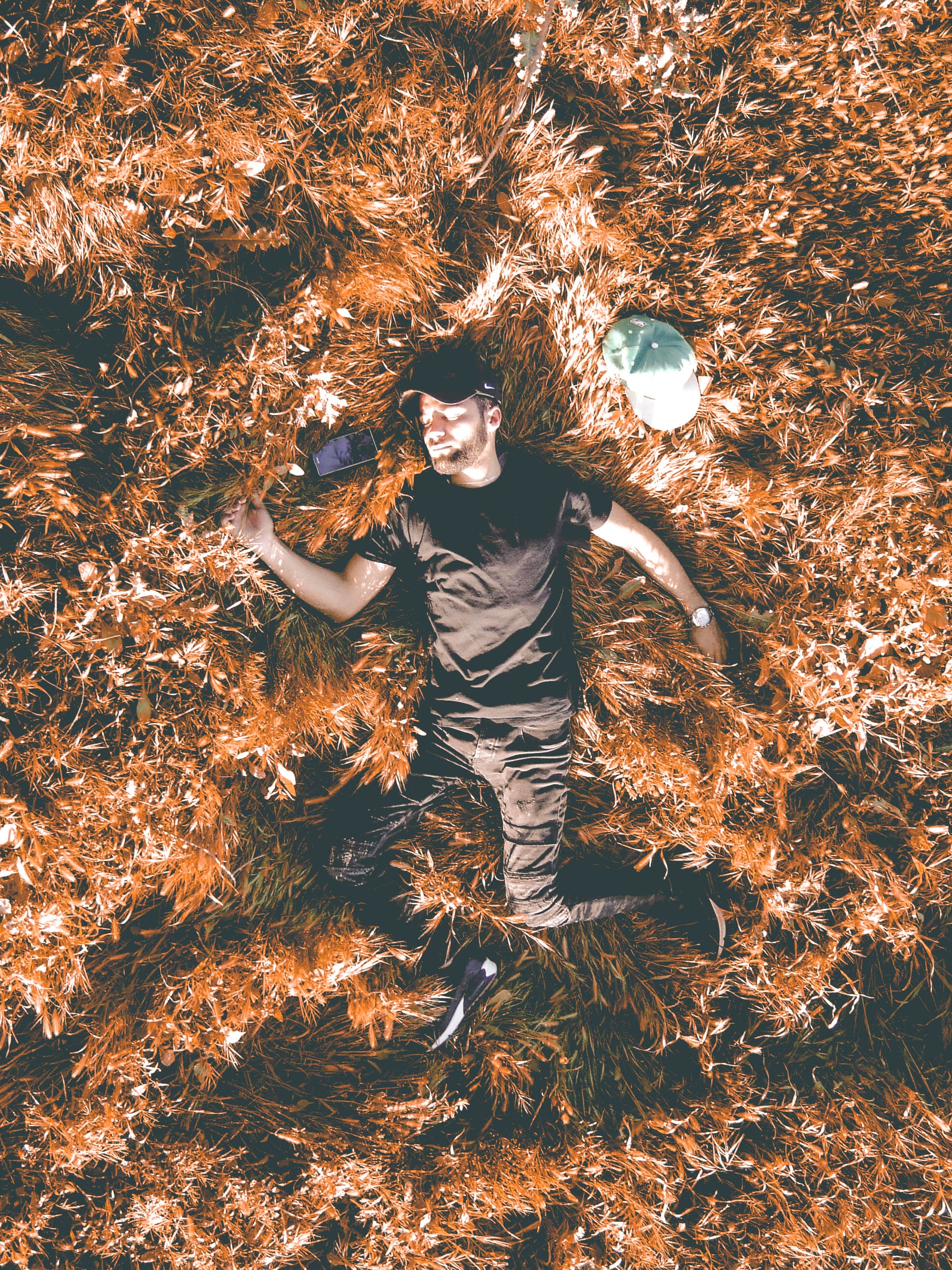 Man in Black Crew-neck Shirt and Black Pants Laying in Brown Dry Leaf