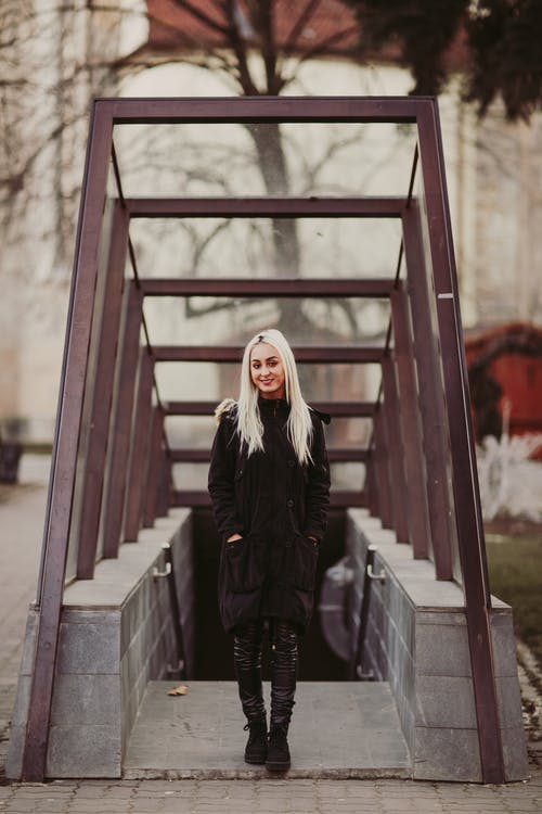 Woman in Black Coat Standing Near Staircase