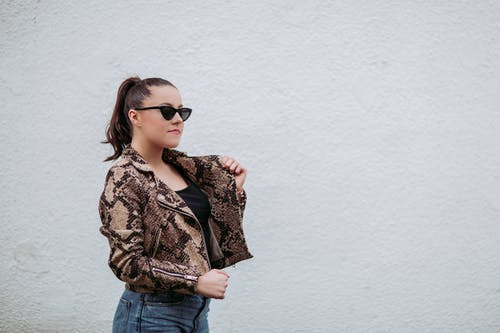 Photo of Woman Wearing Brown-and-black Snakeskin Jacket Beside Wall