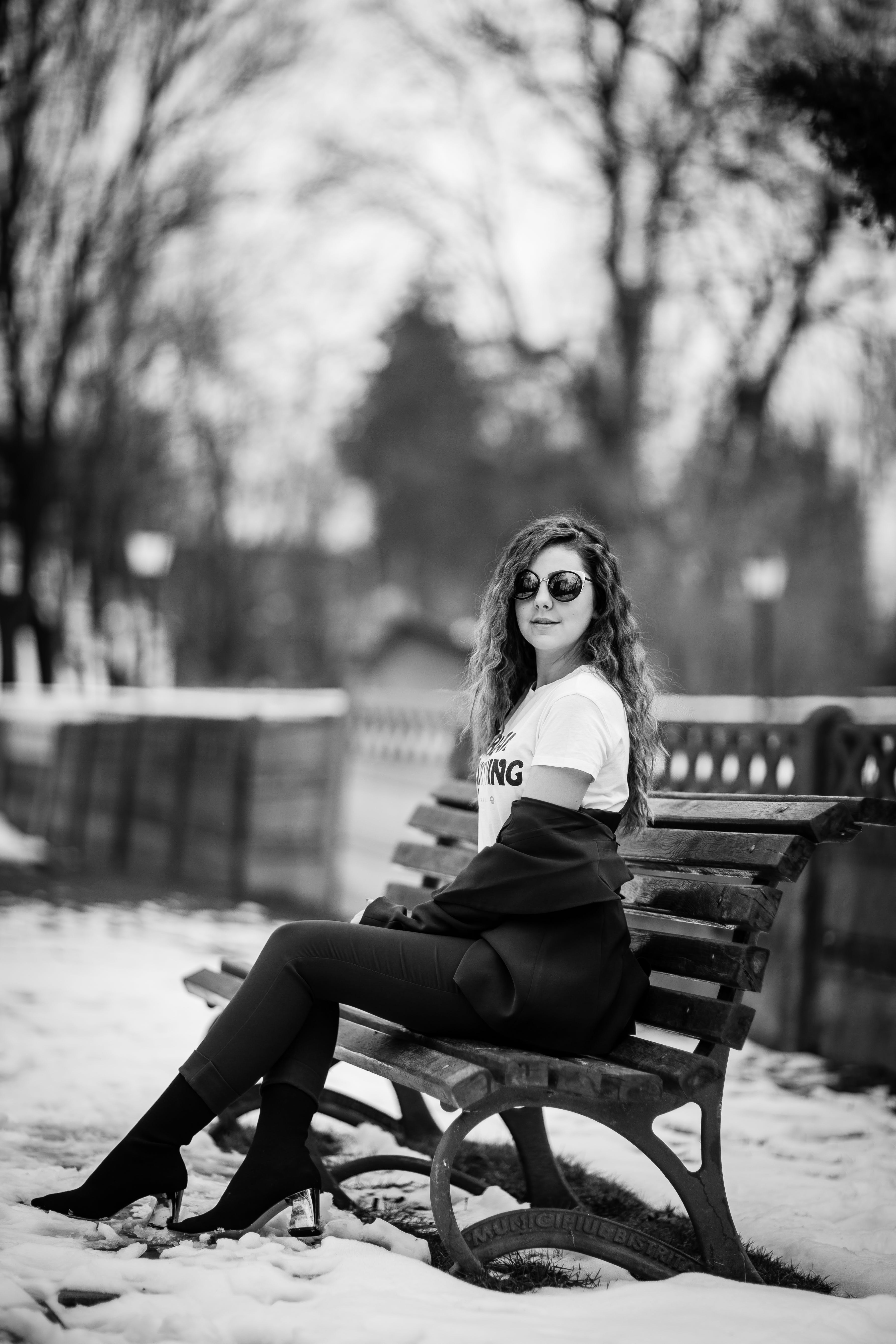 Grayscale Photography of Woman Sitting on Bench