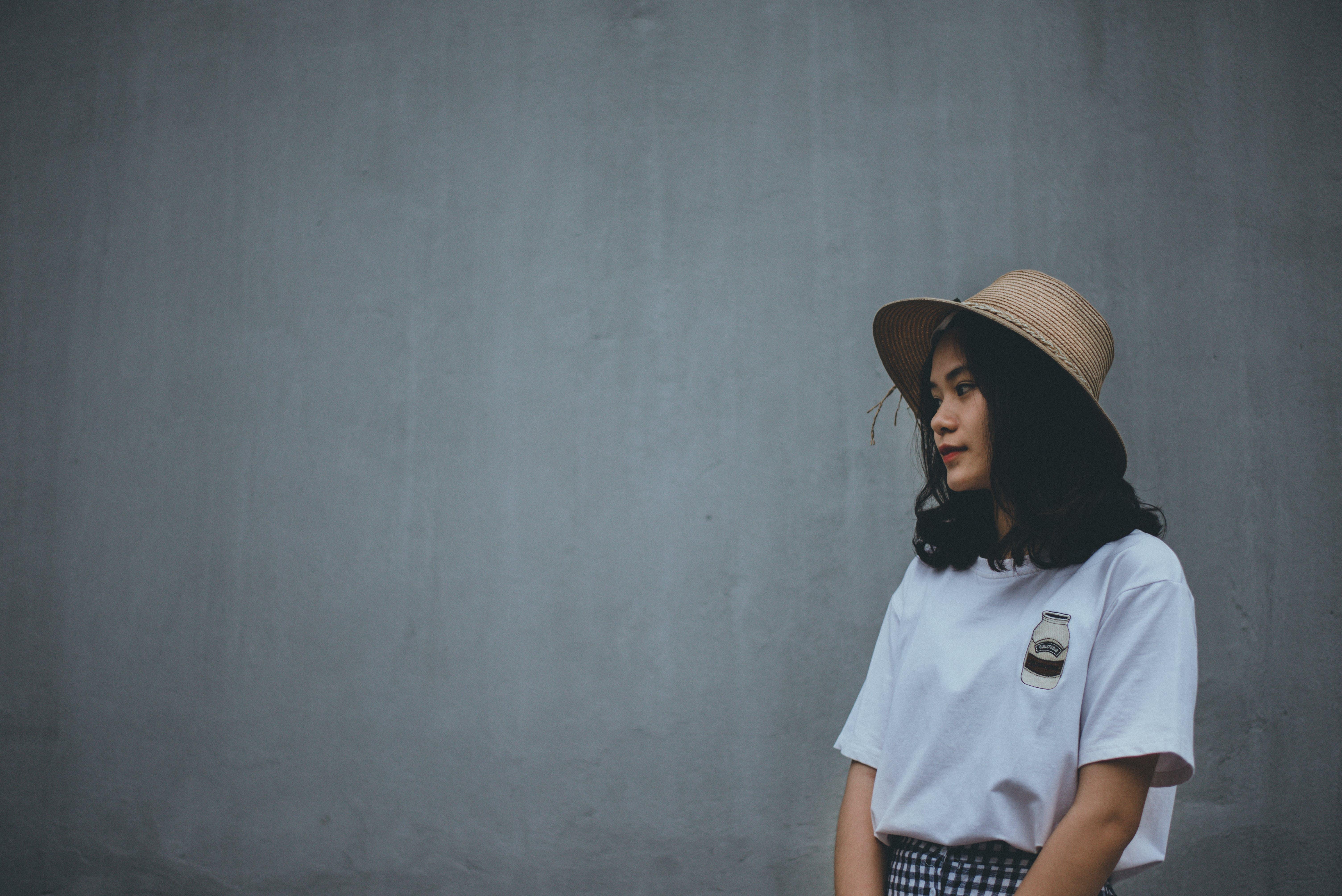 Woman in White Shirt Wearing Brown Hat