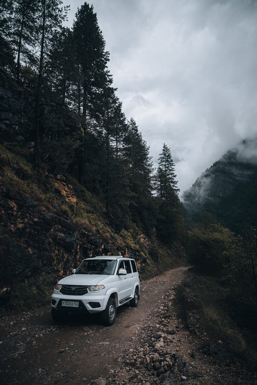 White 4x4 Car on Dirt Road in Mountains