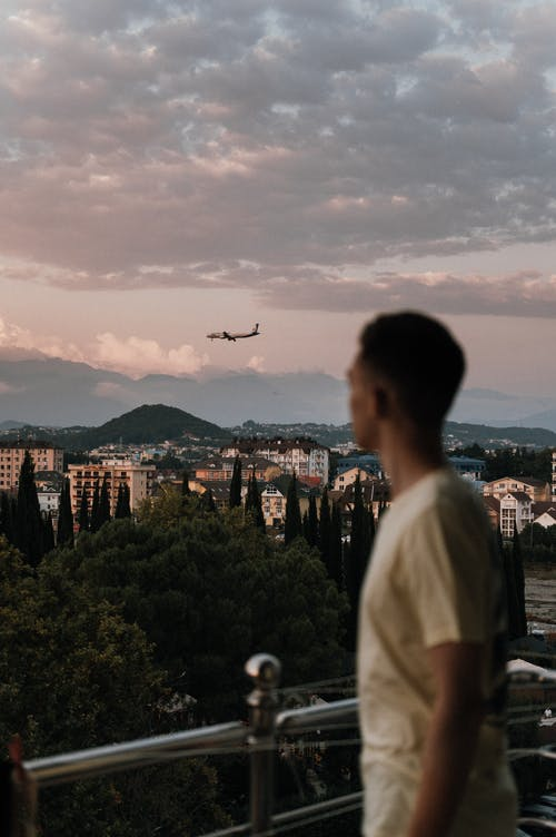 Man Looking at Flying Airplane