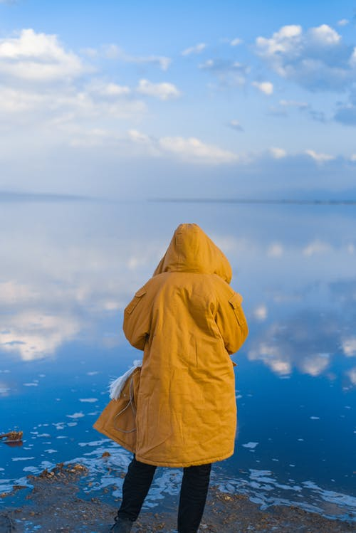 Person in Yellow Hoodie Standing on Seashore