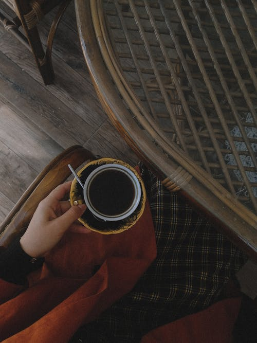 Woman Holding Coffee at Table