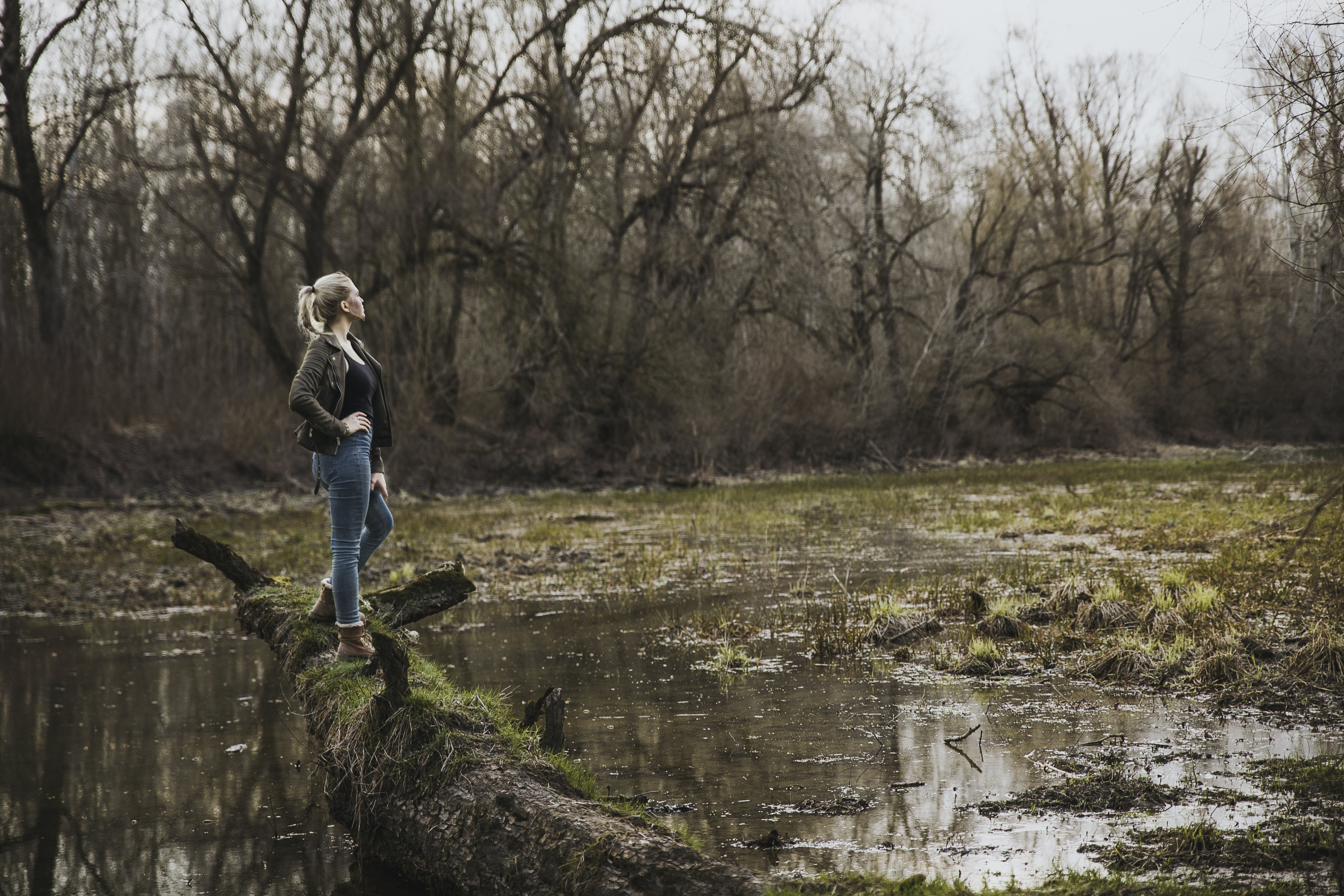 Woman Standing on Driftwood Above Body of Water