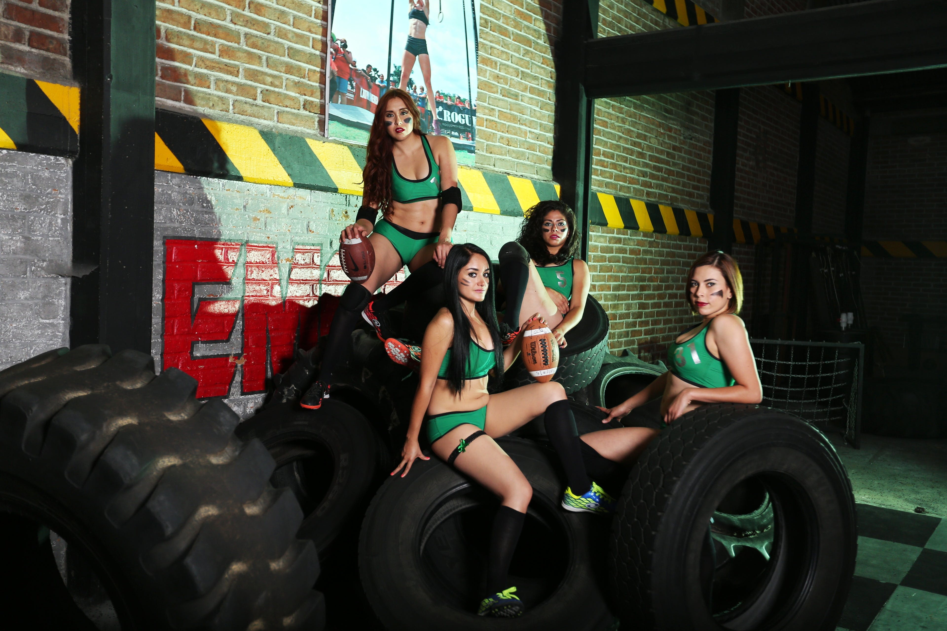 Four Women on Green Sport Bra and Shorts Near Tires
