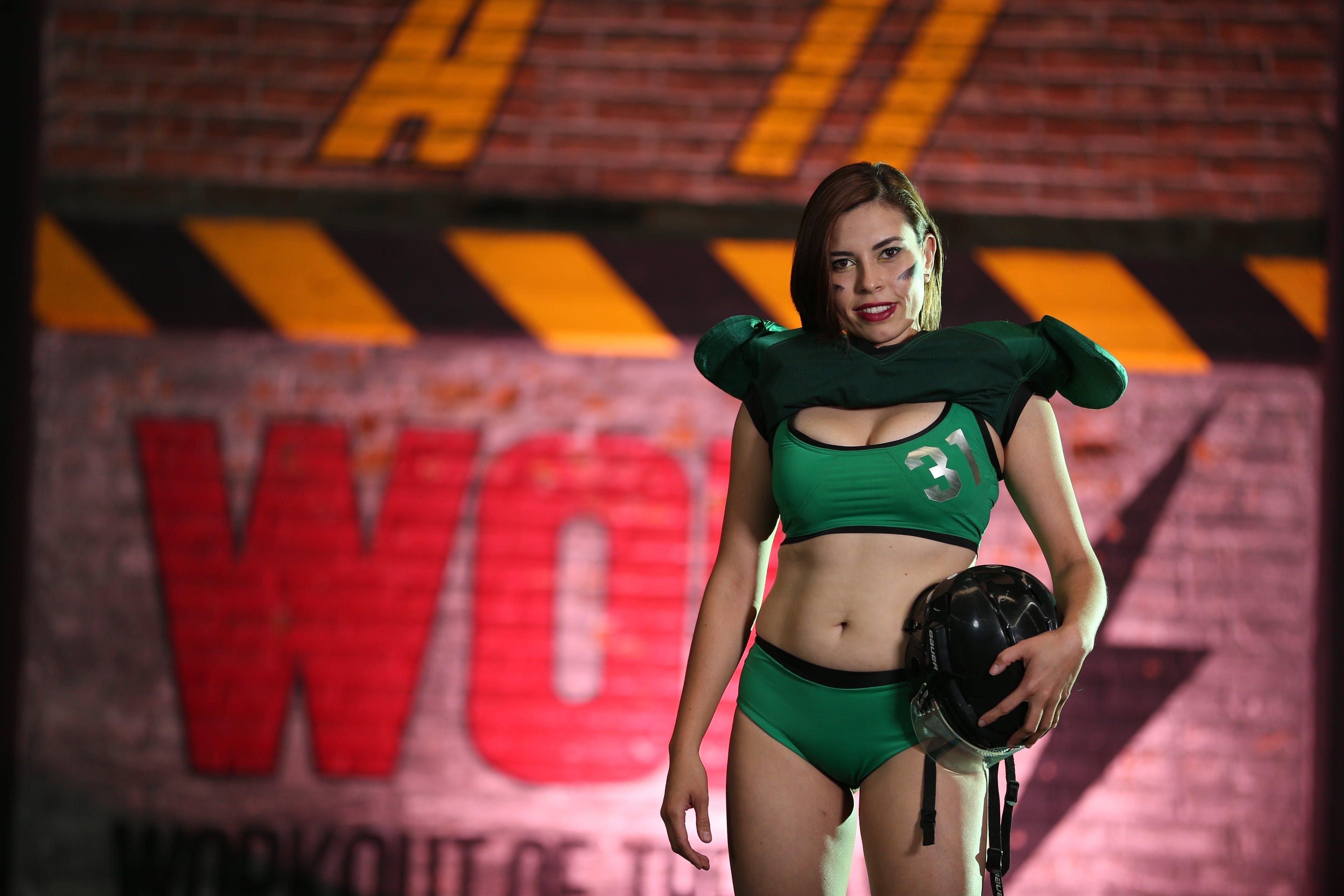 Woman in Green Jersey Set Standing Near Maroon Wall