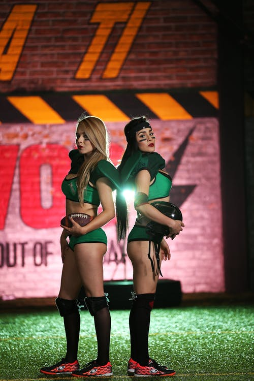 Two Women Wearing Green Crop Top Leaning on Each Other While Taking Photo