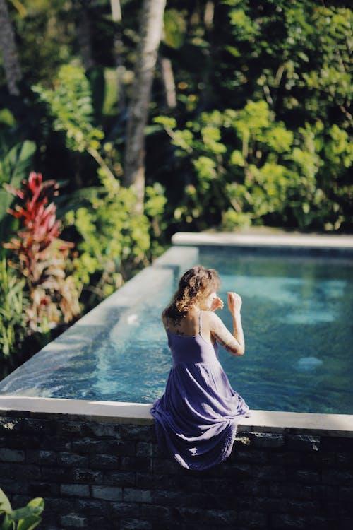 Woman Sitting on Swimming Pools Edge