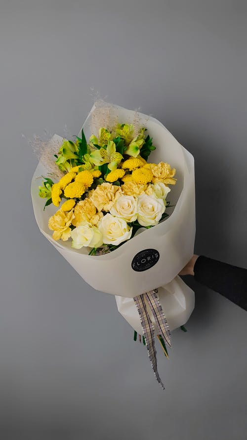 Unrecognized Hand Holding Bouquet of Yellow Flowers