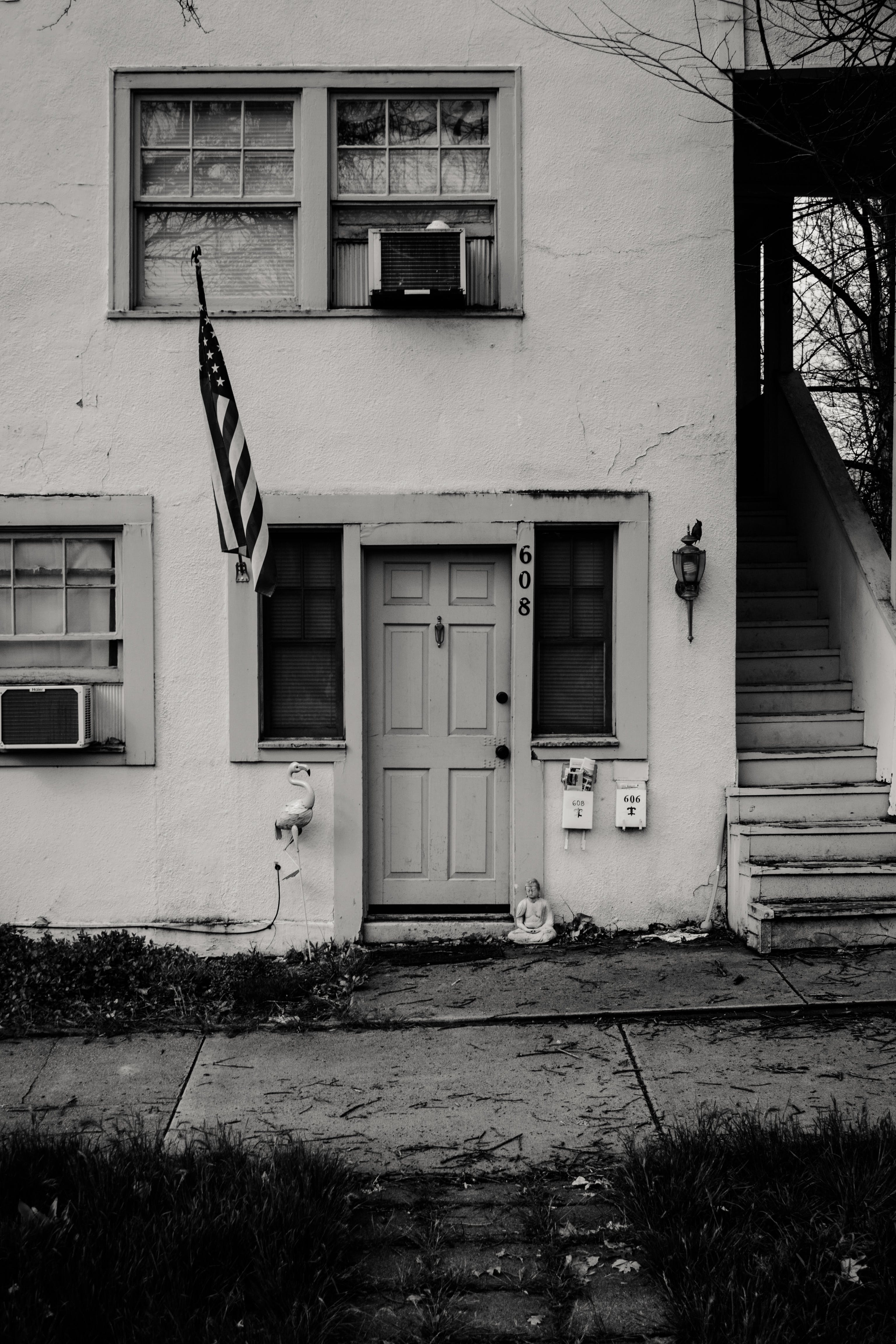 Grayscale Photo of Concrete House With Usa Flag