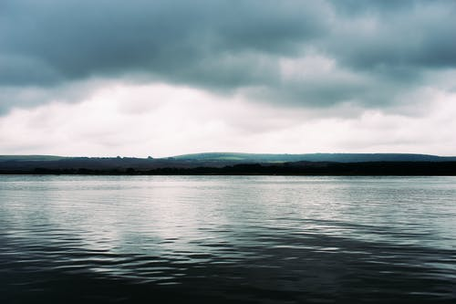 Body of Water Under Cloudy Sky