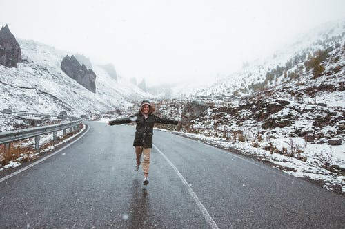 Woman Running on Road in Snowy Mountains