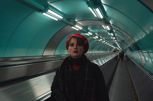 Woman in Red Beret on Moving Walkway