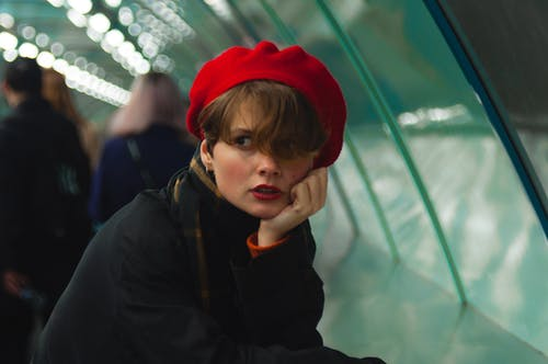 Woman in Red Beret Leaning on Railing