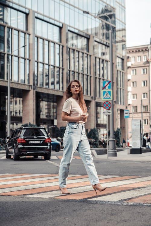 Woman in White Shirt and Blue Denim Jeans Walking on Pedestrian Lane