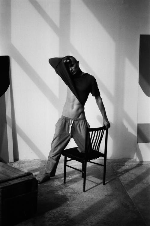 Grayscale Photo of Man in Long Sleeve Shirt and Pants Standing on Wooden Seat