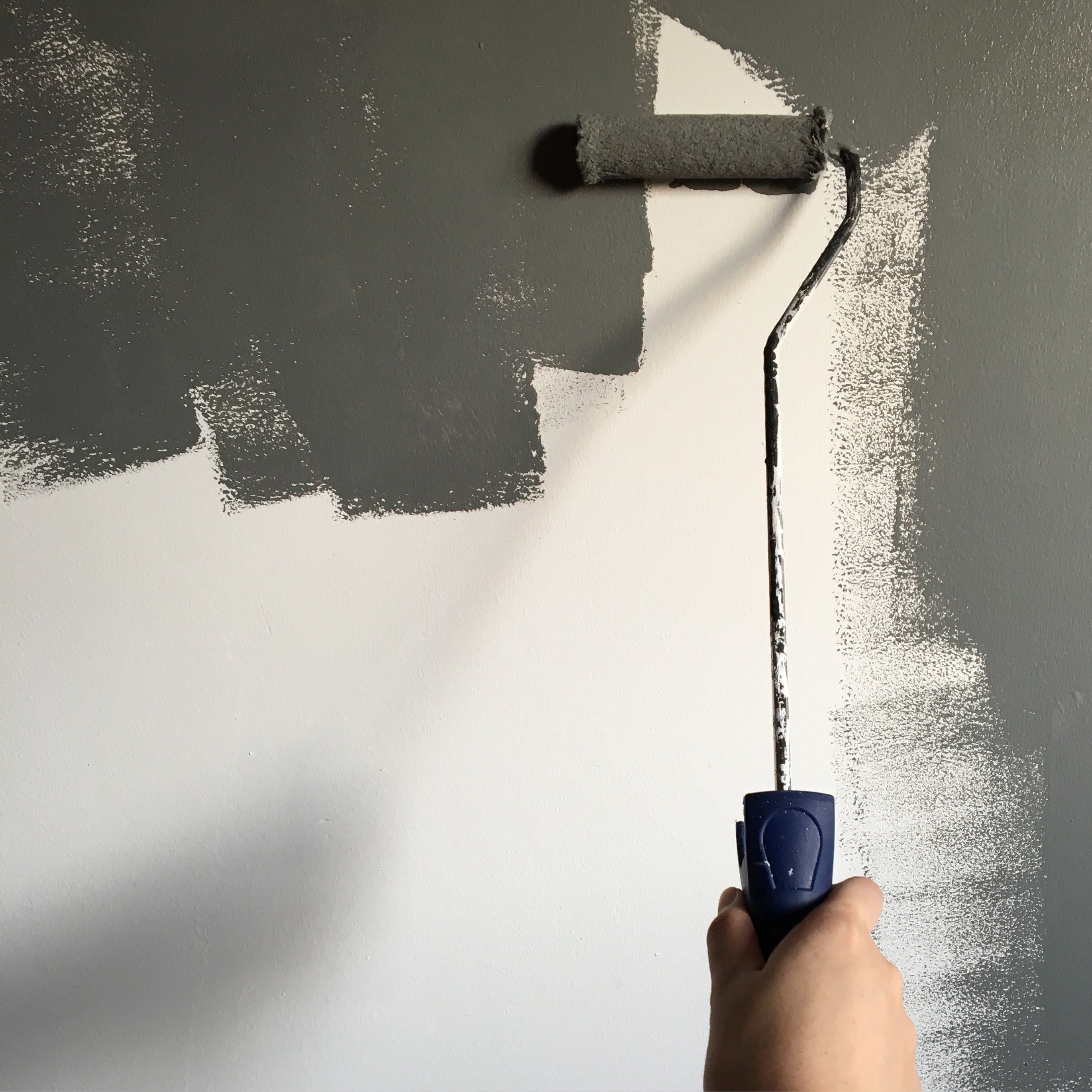 Person Holding Paint Roller While Painting the Wall
