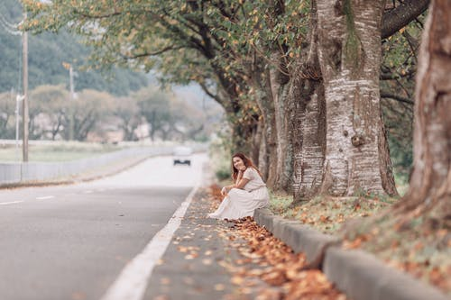 A Female Sitting on Curb Next to a Road