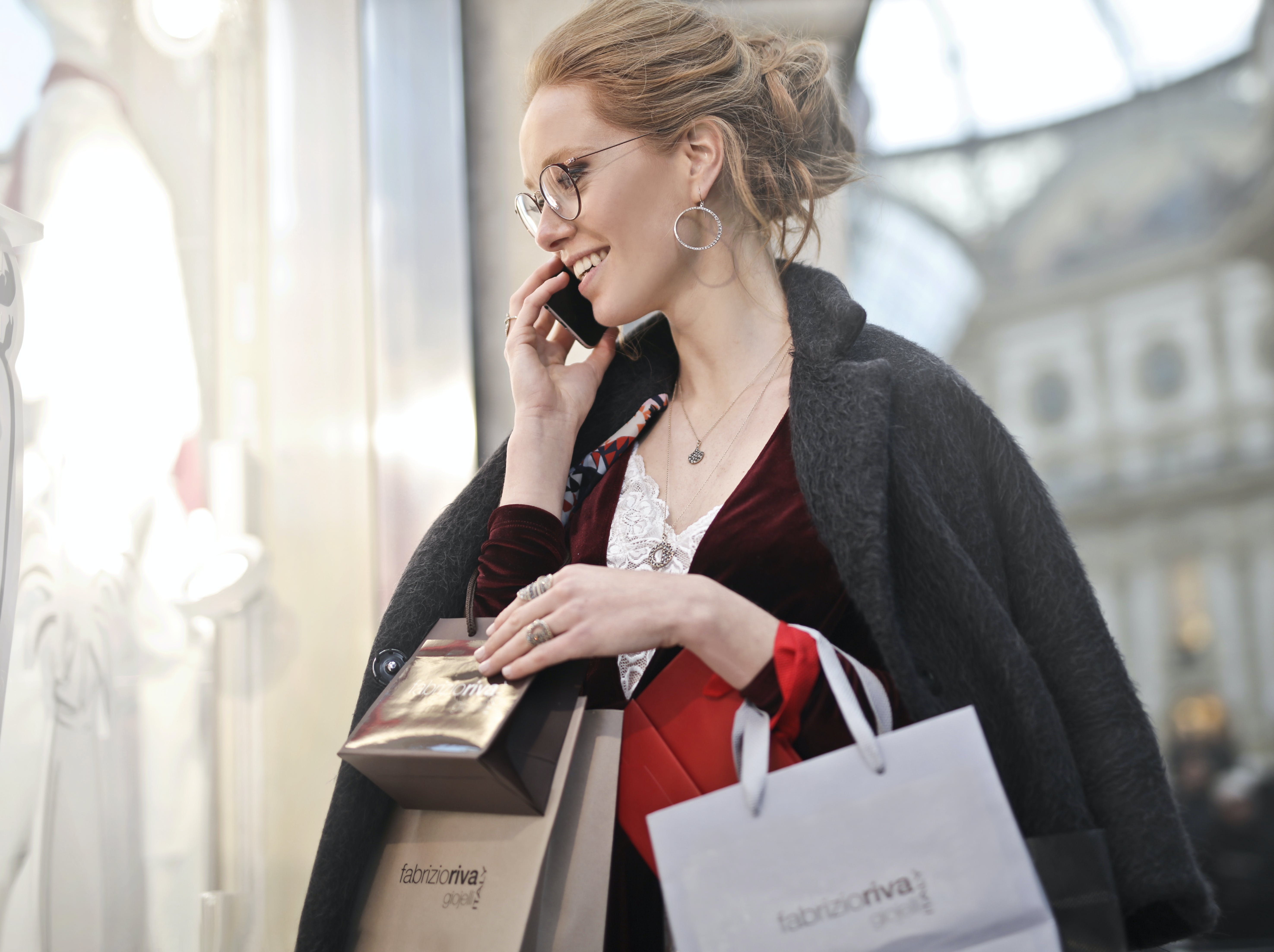 Woman Carrying Paper Bag and Holding Phone