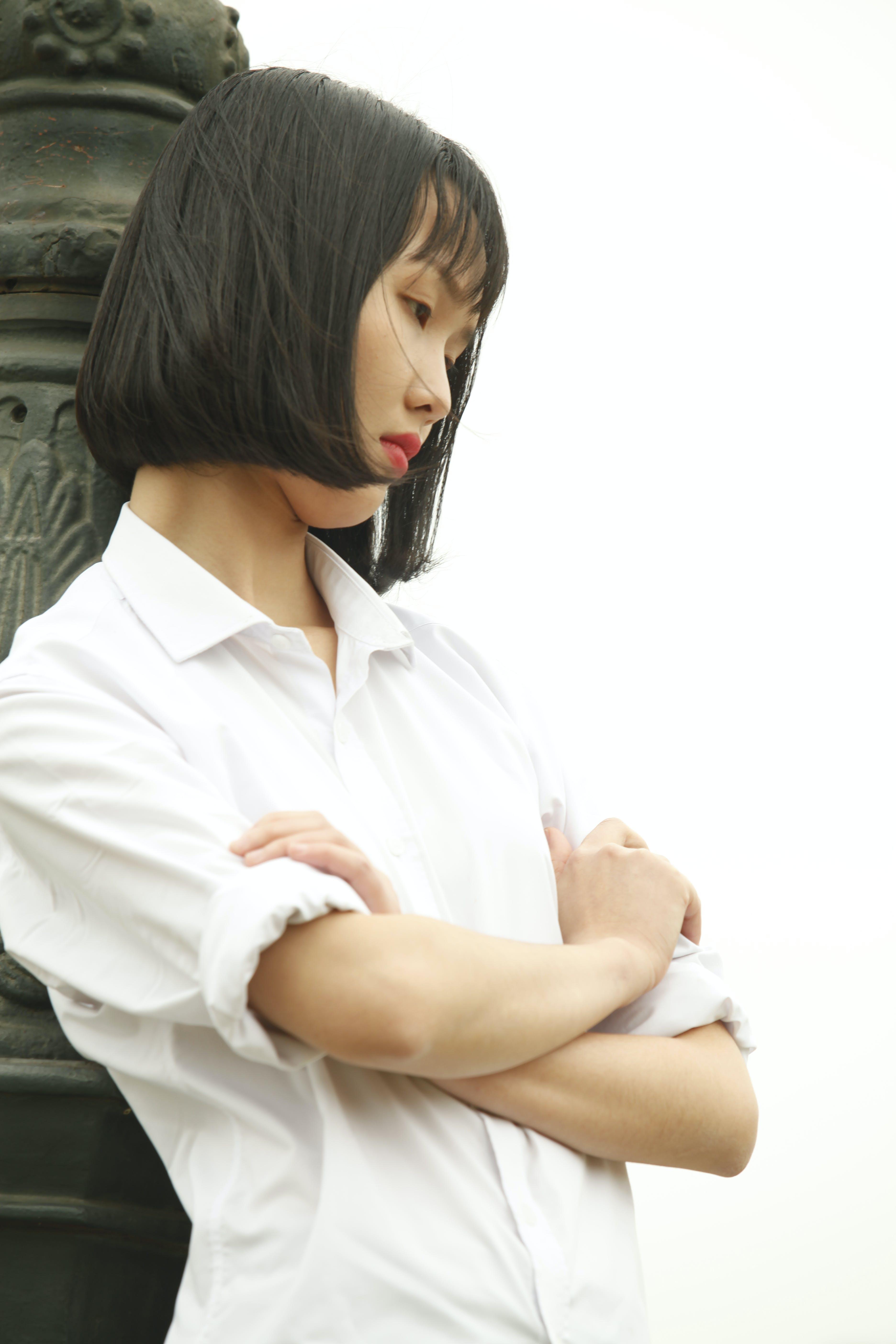 Woman Wearing White Dress Shirt Standing Near Concrete Statue
