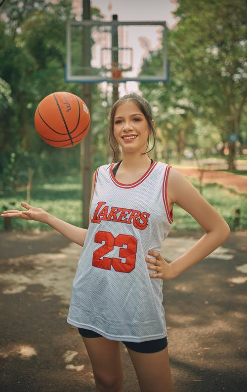 Woman in LA Lakers T-shirt and with Basketball Ball