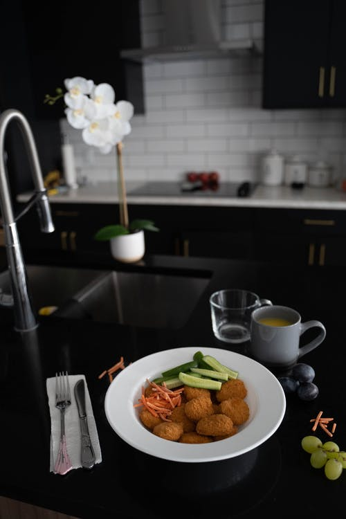 Plate Full of Fried Snacks and Vegetables on Kitchen Worktop