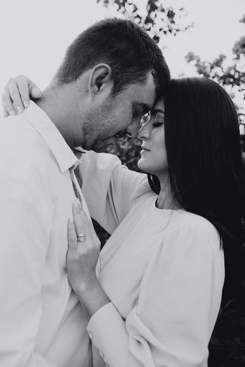 Man in White Dress Shirt Kissing Woman in Black and White Photo