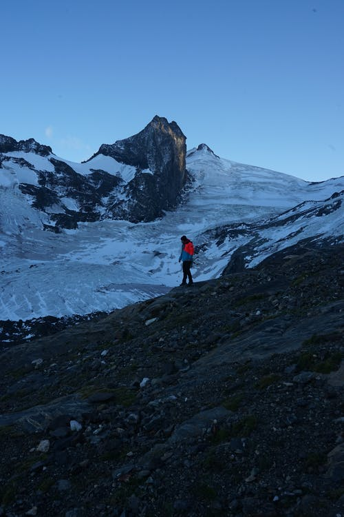 Person in Red Jacket and Black Pants Standing on Rocky Mountain