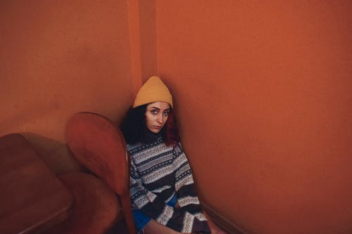 Woman in Winter Hat and Sweater Sitting on Floor in Corner of Room